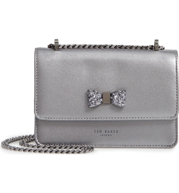 da22e86839 A glittery bow puts a ladylike finish on a leather bag polished with a  pull-through chain strap that can be doubled or lengthened
