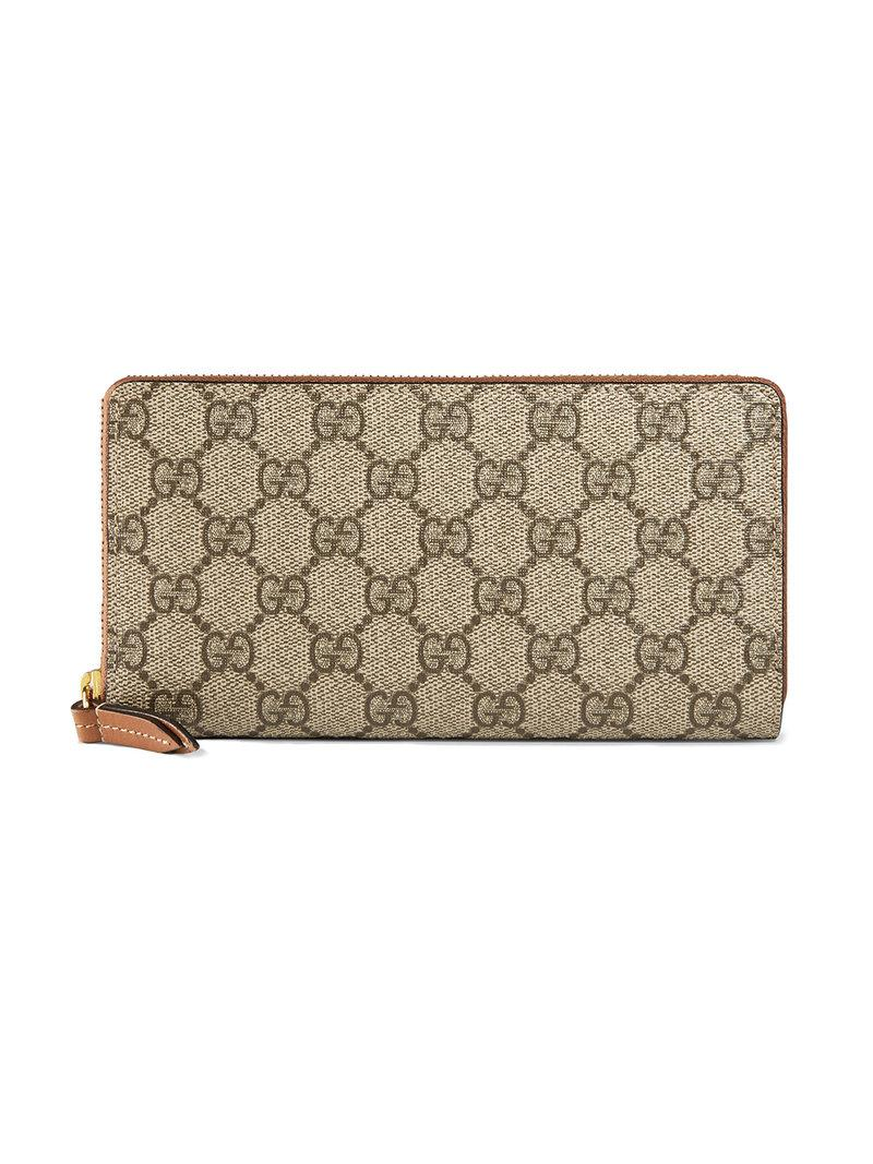 d8f7ebf6d7e A GG Supreme canvas zip around wallet with a brown leather zipper pull  detail. Beige ebony GG Supreme canvas
