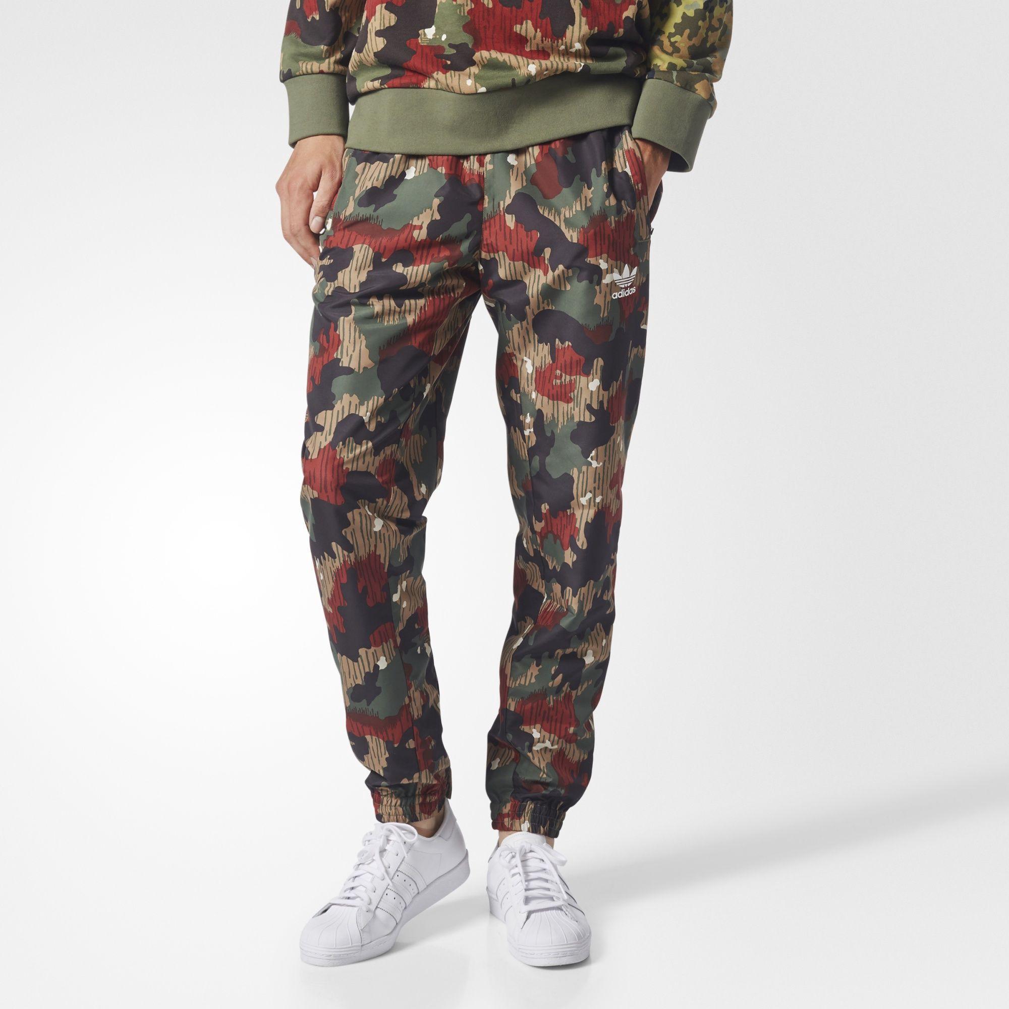 9298f8330b2f ADIDAS ORIGINALS. Originals Pharrell Williams Hu Hiking Wind Pants in Camo