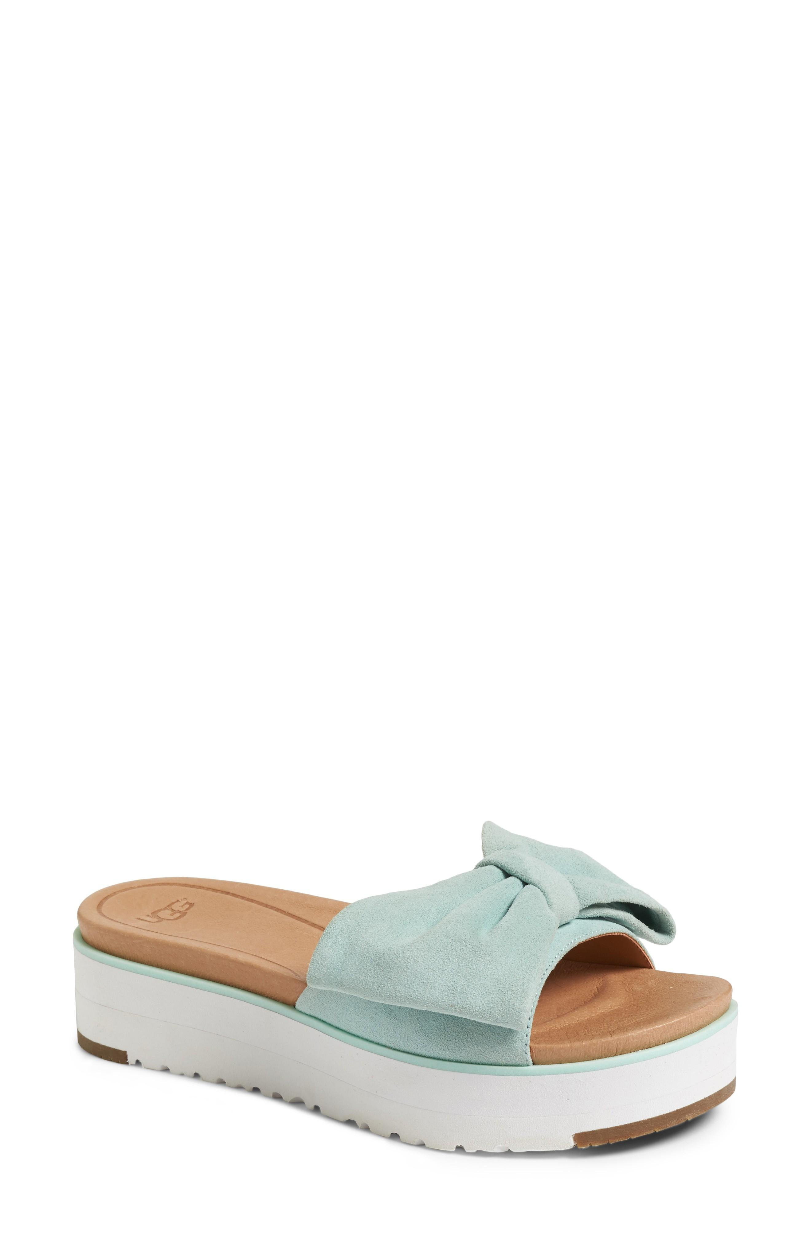 7b8f90ac5ac An oversized bow graces the top of a playful slide sandal grounded by a  platform Treadlite by UGG sole for added cushioning