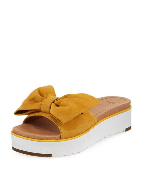 a87a3674cc7 An oversized bow graces the top of a playful slide sandal grounded by a  platform Treadlite by UGG sole for added cushioning