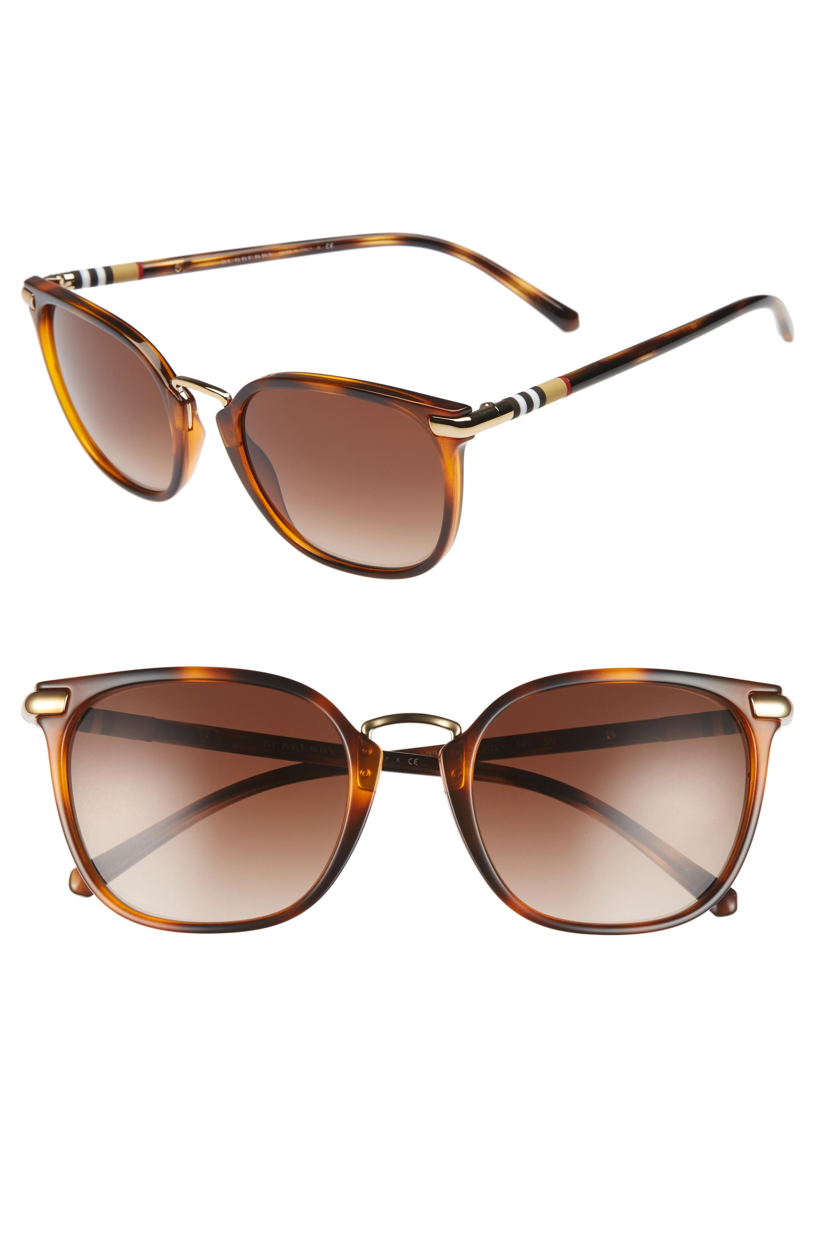 4012083cc3366 A polished metal bridge highlights the frames of polished Italian sunglasses  fashioned with gradient lenses and Burberry checks at the temples.