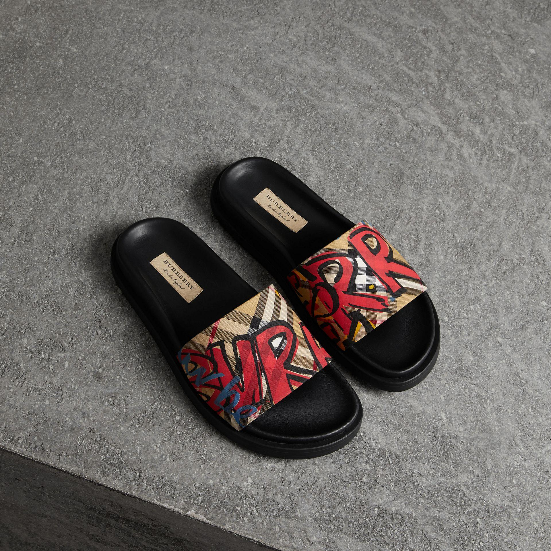 da0b3133fbe0 BURBERRY. Graffiti Print Vintage Check And Leather Slides in Antique Yellow