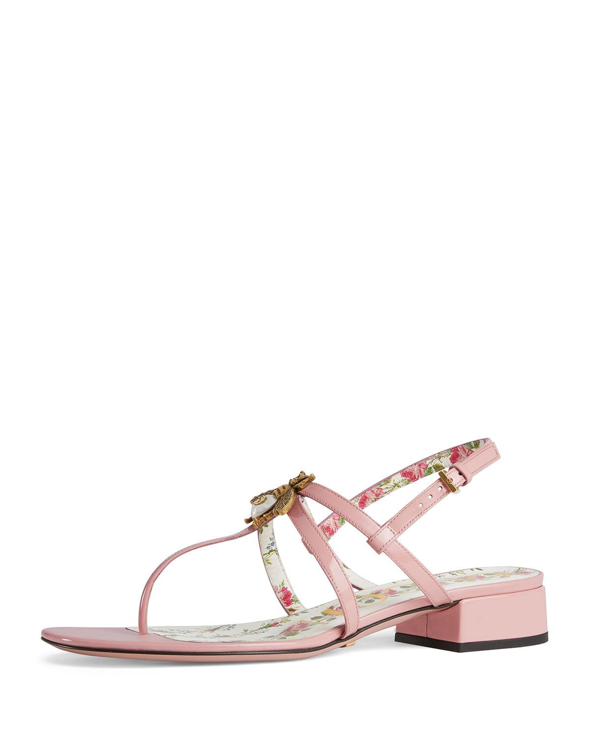 856214b4cbdf Gucci s light pink patent leather thong sandals are styled with a low-cut  block heel and embellished with an antiqued brasstone metal and glass ...