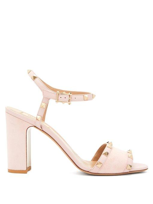 4d60df868b47 ... an open-toe sandal silhouette in soft suede with a stud-adorned ankle  strap to keep them in place and a comfortable block heel.
