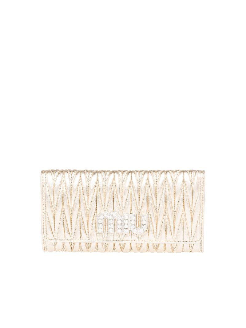 438593ba24e Gold-tone nappa leather matelassé wallet from Miu Miu featuring a foldover  top with snap closure