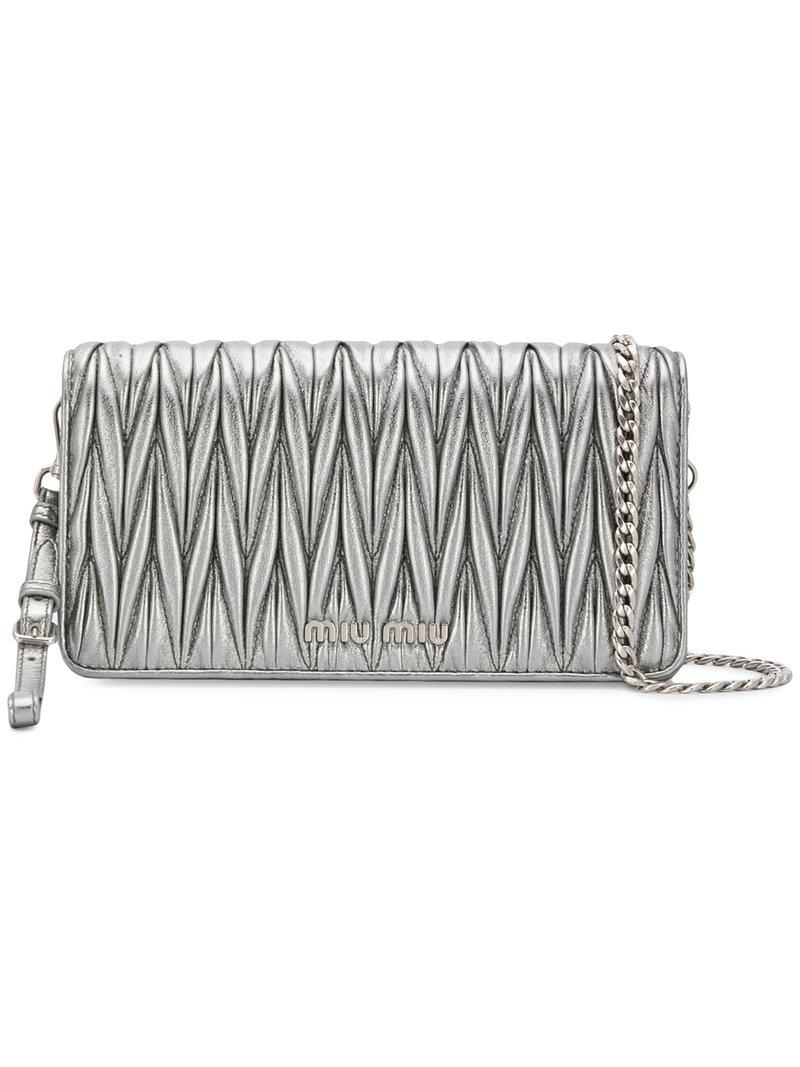 feda0b36b625 Classic silhouettes and timeless accessories are rooted in a free-spirited  femininity. This silver-tone leather Matelassé clutch bag from Miu ...