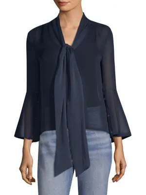 3489b801b4580 Whimsical silk blouse with wide flared cuffs and a tie at the neckline. V- neck with self-tie. Long sleeves. Button cuffs. Button front. High-low hem