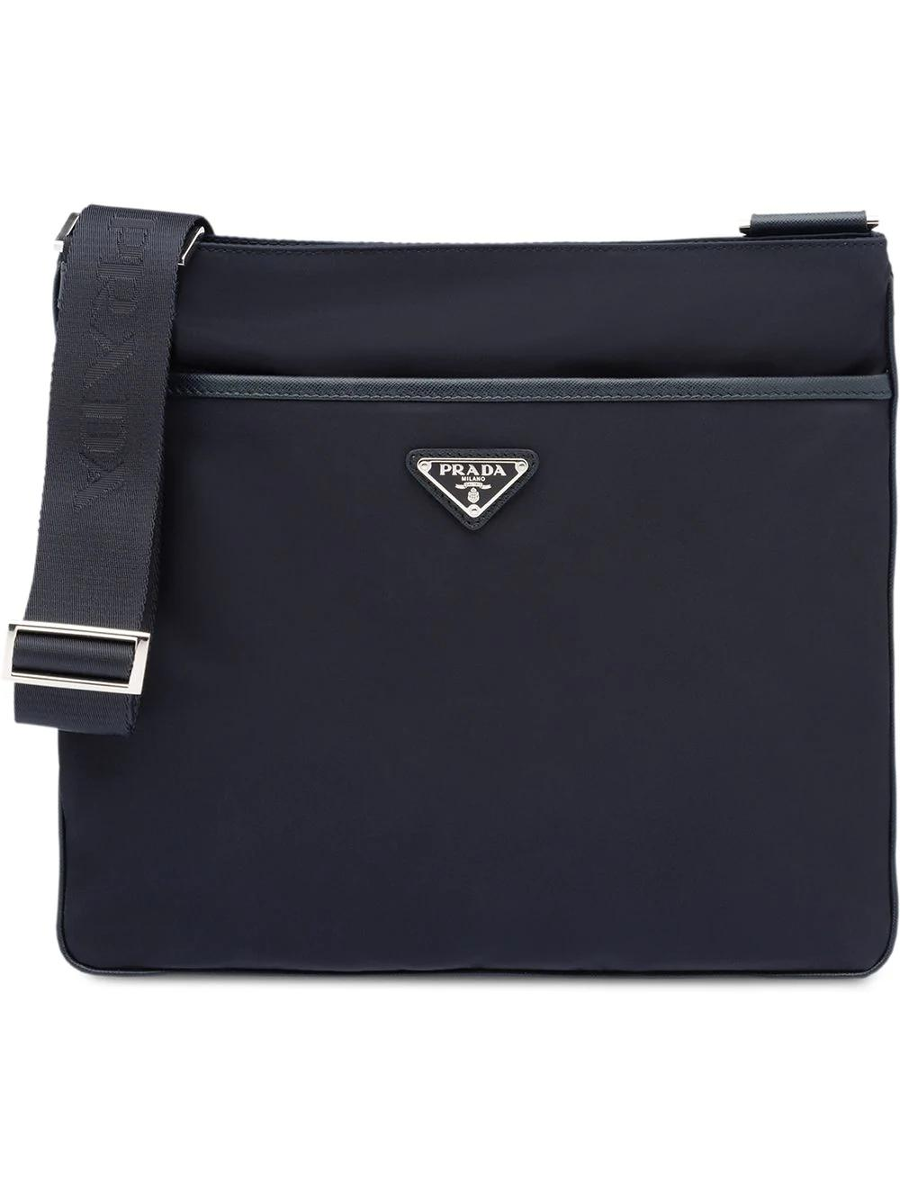 428c4083851c Crafted in Italy, this blue logo plaque messenger bag from Prada features  an adjustable shoulder strap, ...